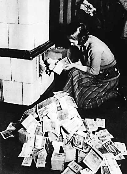 woman burning stacks of worthless currency in her stove for heat in Weimar